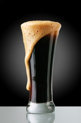 Glass of dark beer with froth