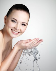 Beautiful smiling young woman washing her face with water - studio shot