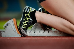 Detailed view of a female sprinter in the starting blocks