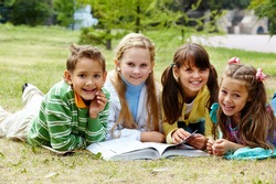 Portrait of cute kids lying on lawn and looking at camera with open book near by