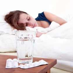 Glass of water and two strips of pills on a bedside table, with a sick woman sleeping in the background. Focus on the glass and strips of pills