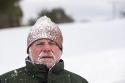 A man wearing a beanie cap and covered with snow is looking at the camera with an unhappy expression. Horizontal shot.