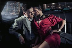 seductive woman with her hand on her hip sitting against man in a car