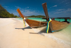 Two traditional longtail boats parked on a white sand beach surrounded by crystal clear turquoise water on a sunny, blue sky day on the Thai paradise island of Ko Lipe, Thailand. Horizontal copy space