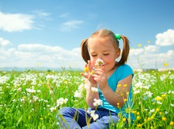 Little girl is smelling flowers while sitting on green meadow