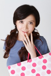 Attractive shopping woman of Japan holding bags and looking at you, half length closeup portrait on grey studio background.