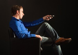Handsome man sitting on the armchair in the dark changing TV channels with remote control