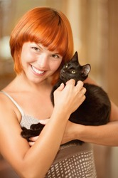 Young beautiful red-haired smiling woman has control over fluffy black cat.
