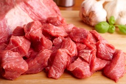Raw beef on wooden cutting board with garlic  and bazil