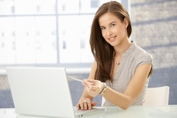Cheerful young woman pointing at screen while reading on laptop computer, smiling at camera.?