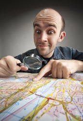 Funny nerd tourist discovering map with magnifier