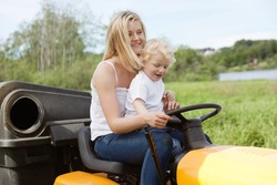 Smiling young woman with adorable child sitting on lawn mower