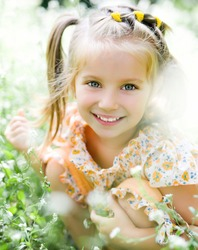 Cute little girl  on the meadow in summer day