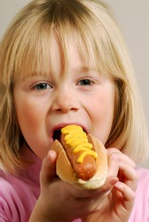 Little girl eating a hot dog.Kid eating hot dog.
