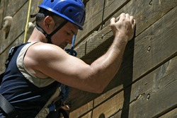 Man on a climbing wall who is showing strong biceps as he reaches for the next hold.