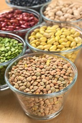 Lentils and other legumes (split peas, canary beans, kidney beans, chickpeas) in glass bowls (Selective Focus, Focus one third into the lentils)
