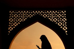 silhoutte of muslim woman praying during fasting holy month of ramadan