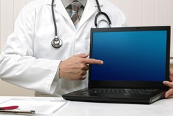 Medical professional holding a laptop pointing at a computer screen