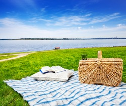 Picnic blanket and basket in the grass with beautiful lake view