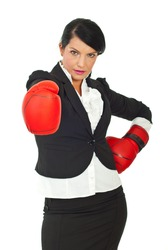 Businesswoman with attitude wearing boxing gloves and being prepared for competition against white background,selective focus on glove