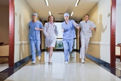 Team of surgeon and nurse running in hallway of hospital