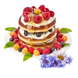 Pancakes stack with fresh berries and honey on white background