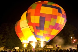 Hot Air Balloon festival with night glow and drifting smoke from fireworks.