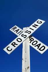Brilliant blue skies frame rustic railroad crossing sign.  Low angle shot with a lot of blue sky showing and copy space available.