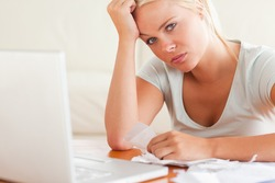 Stressed woman doing paperwork in her living room