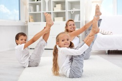 Healthy morning stretching - woman with kids doing gymnastic exercise at home