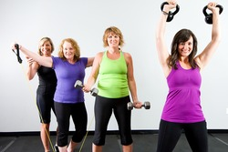 Healthy, active group of mature women working out with various equipment at a gym.