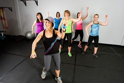 An aerobics and dance class for women at a gym.