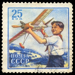USSR - CIRCA 1958: A stamp printed in USSR shows boy who holding airplane model, circa 1958.