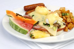 Mushroom ham and cheese eggs benedict with sausage and potatos