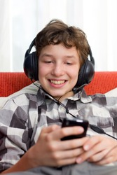 A preteen boy having fun as he listens to his mp3 player through big headphones on his head. He's seated on an orange couch with white pillows and he's wearing a checkered dress shirt.