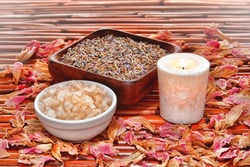 Aromatherapy bath salts and dry lavender seeds in a bowl with scented candle and fragrant flower petals on bamboo for a relaxing scent immersion bathing therapy wellness session in a relaxation spa