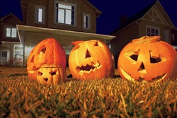 Four pumpkins of Halloween lie on grass before cottage.