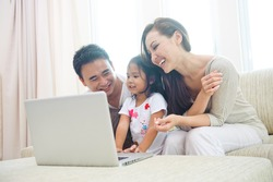 Happy Attractive Asian Family using laptop with daugther