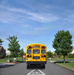 Children Crossing Traffic Sign School Bus with Happy Little Boy Inside on Suburban Residential Neighborhood Street
