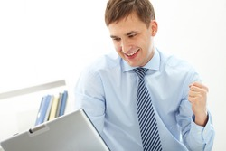 Portrait of happy businessman expressing triumph in front of laptop