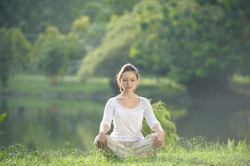 Attractive Healthy Asian Woman meditating in the park