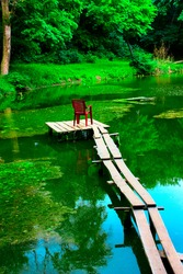 Wooden dock with chair on calm summer lake