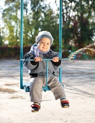cute baby boy playing on swing in autumn park