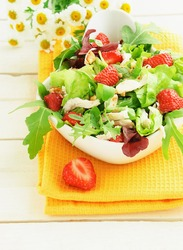 Green salad with strawberry, chicken, nuts, cheese in a white bowl on the table
