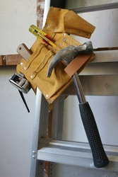 Builders tool belt hanging on a ladder.