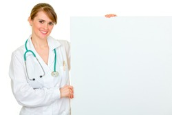 Smiling medical female doctor holding blank billboard isolated on white