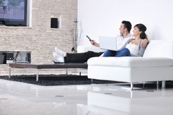 Relaxed young  couple watching tv at home in bright living room