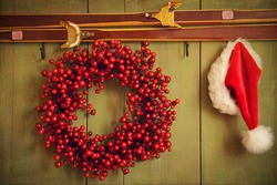 Christmas wreath with Santa hat hanging on rustic wall