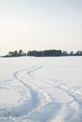 The traces left on snow from the lorry (on a sunset, traces pass through a field, instead of through road)