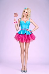Young glamour barbie looking girl with lollipop
